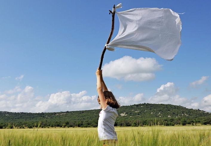 girl-holding-high-a-white-flag-in-wheat-field